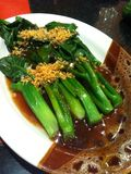 Fried kale in oyster sauce with fried garlic topping Stock Images