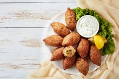 Fried kibbeh with yogurt sauce in a bowl stock images