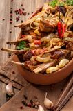 Fried lamb chops with fried onions. Garlic and fresh herbs. A large portion is served on a clay plate and decorated in a rustic style. Close up and vertical royalty free stock image