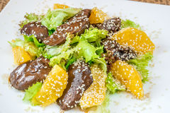 Fried liver with sesame, oranges and salad Stock Photography