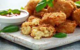 Fried Mac, morsures de macaronis au fromage dans la chapelure avec de la sauce à ketchup sur le conseil en bois blanc image stock