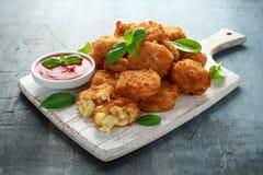 Fried Mac, morsures de macaronis au fromage dans la chapelure avec de la sauce à ketchup sur le conseil en bois blanc image libre de droits