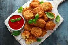 Fried Mac, morsures de macaronis au fromage dans la chapelure avec de la sauce à ketchup sur le conseil en bois blanc photo stock
