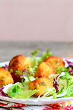 Fried mashed potato balls with salad leaf mix and basil on a plate. Small fried balls made from mashed potatoes Stock Photos