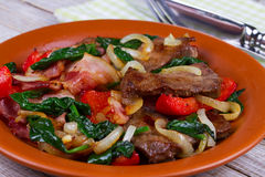 Fried meat, bacon, red paprika pepper and spinach plate. Stock Photos