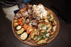 Fried meat and baked vegetables on a wooden board in the hands of a waiter royalty free stock photo