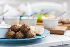 Fried meat balls with mint and apple with white sauce and flat cakes - traditional Greek lunch on a blue plate in a restaurant stock photo