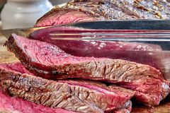 Fried meat with blood with hunting knife. Well done steak closeup. Rustic style. stock photography