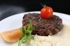 Fried meat cutlet on a plate, with celery puree, garnished with tomato cherry and sour apples, isolated. For a menu royalty free stock photo