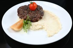 Fried meat cutlet on a plate, with celery puree, garnished with tomato cherry and sour apples, isolated. For a menu royalty free stock photos