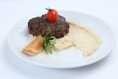 Fried meat cutlet on a plate, with celery puree, garnished with tomato cherry and sour apples, isolated. For a menu stock photos