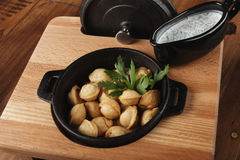 Fried meat dumplings pelmeni, chuchpara. In a black pan. wooden background Stock Photo