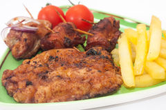 Fried meat with french fries and cherry potato on the plate Stock Photography