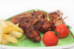 Fried meat with french fries and cherry potato on the plate Royalty Free Stock Photo