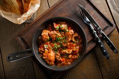Fried meat in a frying pan tomato sauce Royalty Free Stock Photos