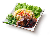 Fried meat ribs in sauce with rice salad... Fried meat ribs in sauce with rice salad and parsley in squared plate over white background Royalty Free Stock Photo