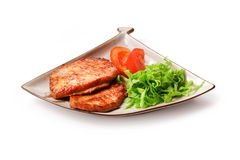 Fried meat with salad and tomato. In squared plate over white background Stock Images