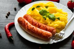 Meat sausages with mashed potatoes in a plate on dark wooden background Stock Image