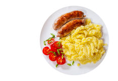 Fried meat sausages with mashed potatoes and vegetables salad in a plate. top view. Isolated on white Royalty Free Stock Images