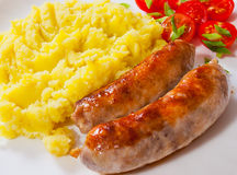 Fried meat sausages with mashed potatoes and vegetables salad. In a plate on wooden table Royalty Free Stock Photography