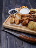 Fried meat slices of chicken wings, ham, fillets with sauce. On a wooden board Royalty Free Stock Image