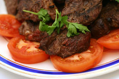 Fried meat and tomatoes Stock Images
