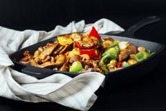 Fried meat and vegetables in cast iron pan. Fried mix of meat and vegetables in cast iron pan Stock Image