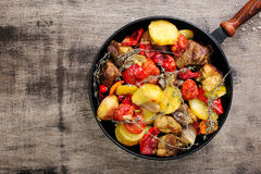 Fried meat with vegetables in cast iron pan Royalty Free Stock Photos