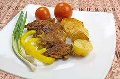 Fried meat. Fried meat with vegetables and potatoes on a white plate stock image