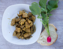 Fried meat on the white plate and garden radish on the slice bre Stock Image