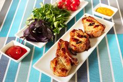 Fried meat on a white plate and a plate with greens. Three slices of grilled pork loin.Next to a plate of herbs and tomatoes.ketchup and mustard Royalty Free Stock Images