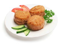 Fried meatballs with cucumbers, tomatoes. Fried meatballs decorated with slices of cucumbers, tomatoes and parsley on the plate over white background Stock Photos