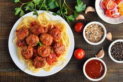 Fried meatballs and spaghetti on white plate. Tomato sauce and spice on wooden table, top view stock image