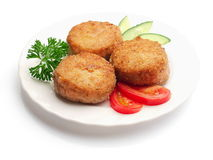 Fried meatballs with tomatoes, cucumbers. Fried meatballs decorated with slices of tomatoes, cucumbers and parsley on the plate over white background Royalty Free Stock Photography