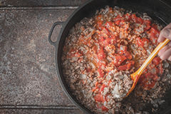 Fried minced meat with onion and chopped tomatoes in the pan on the metal background Royalty Free Stock Photos
