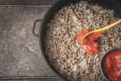 Fried minced meat with onion and chopped tomatoes  in the pan top view Royalty Free Stock Photography