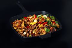 Fried meat and vegetables in cast iron pan. Fried mix of meat and vegetables in cast iron pan on dark background Royalty Free Stock Photos