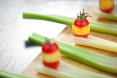 Fried mozzarella in Tomato sandwich. Little mozzarellas rolled in corn flour, fried and sandwiched in between cherry tomatoes, served on celery. Shallow depth of Stock Images
