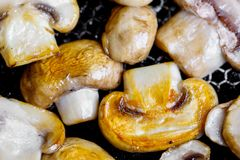 Fried mushrooms in a hot frying pan on an electric stove stock photography