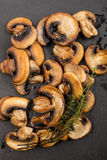 Fried mushroom slices and thyme on slate Stock Photography