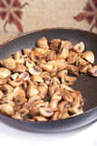 Fried mushrooms in a pan. Fried champignon mushrooms in a hot pan with oil Royalty Free Stock Images