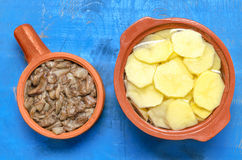 Fried mushrooms and raw chopped potatoes Royalty Free Stock Images