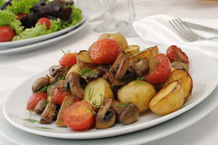 Fried mushrooms with sliced tomatoes and potatoes Royalty Free Stock Photography