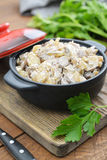 Fried mushrooms with sour cream. In ceramic casserole on wooden background Stock Photos