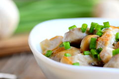 Fried mushrooms with sour cream sauce and fresh green onions in a bowl. Simple and delicious vegetarian recipe Royalty Free Stock Images