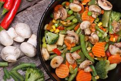 Fried mushrooms with vegetables in a pan top view Royalty Free Stock Photo