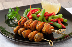 Fried mussels with onions on skewers c garnish of green beans and paprika Stock Photos