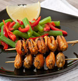 Fried mussels with onions on skewers c garnish of green beans and paprika Stock Image