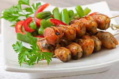 Fried mussels with onions on skewers c garnish of green beans and paprika Stock Photography