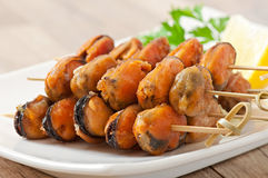 Fried mussels with onions on skewers with lemon and parsley Stock Photo